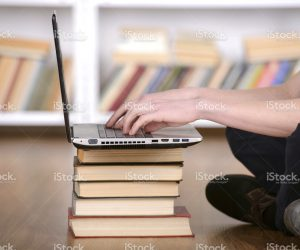 Student at Laptop on Stack of Books